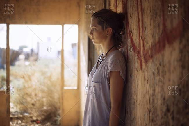 Woman leaning against wall in abandoned building