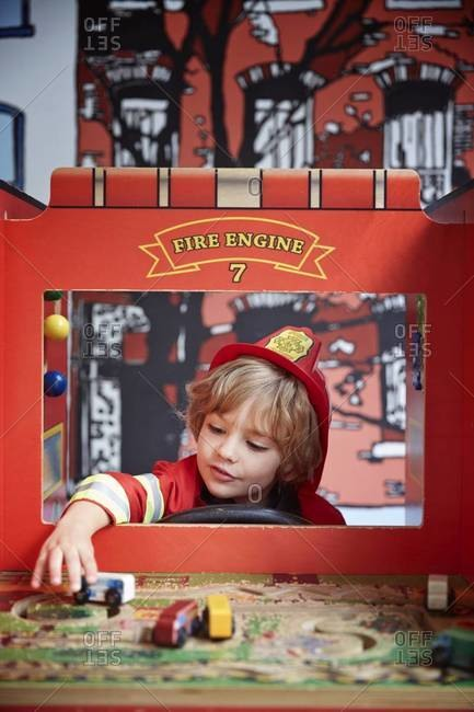 Boy in fireman costume playing with toys