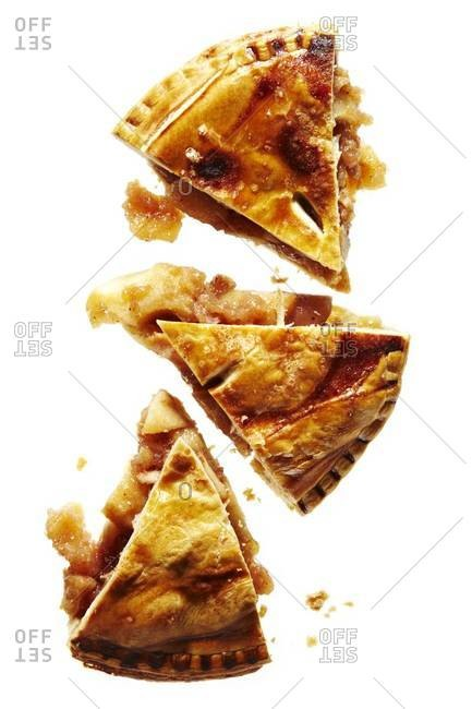 Overhead view of three slices of apple pie on white background