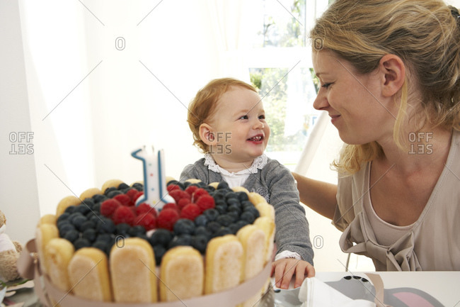 Mother and daughter celebrating little girl's first birthday with self-made fancy cake