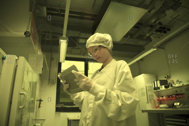 Woman with digital tablet working in a clean room unit