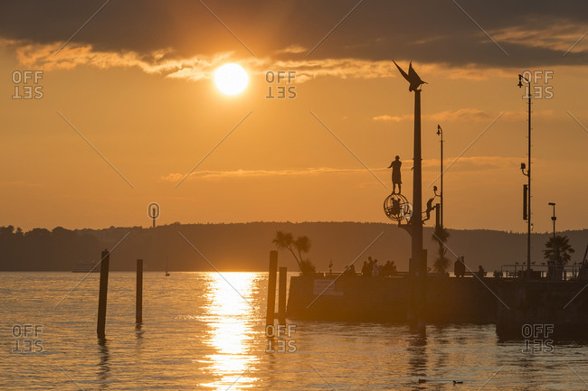Harbor entrance with sculpture magical pillar at sunset, Lake Constance