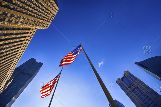 Chicago, USA - November 14, 2014: View to facades of skyscrapers and two American flags from below