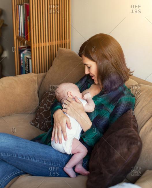 Mother nursing infant on a sofa