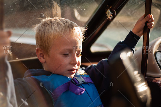 A boy holds on near the windshield of a boat