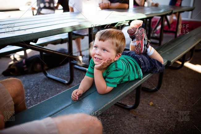 A boy lays on a picnic bench and talks to his dad
