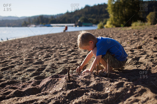 A boy arranged natural objects on the beach