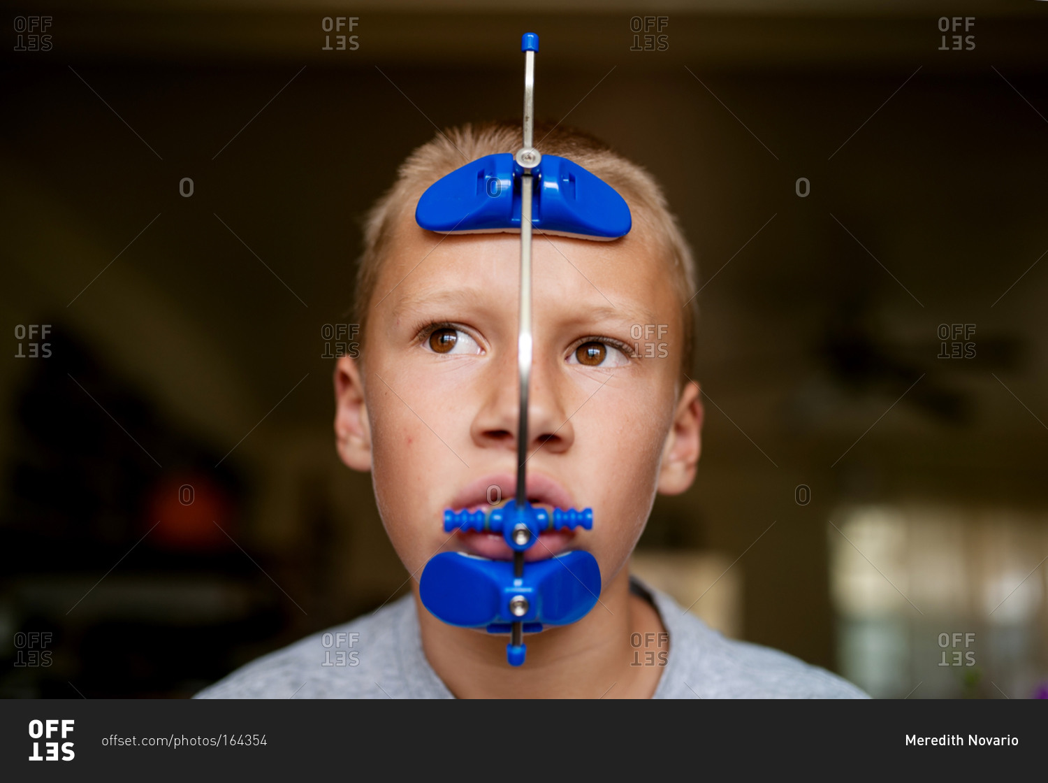 Boy wearing orthodontic headgear stock photo - OFFSET