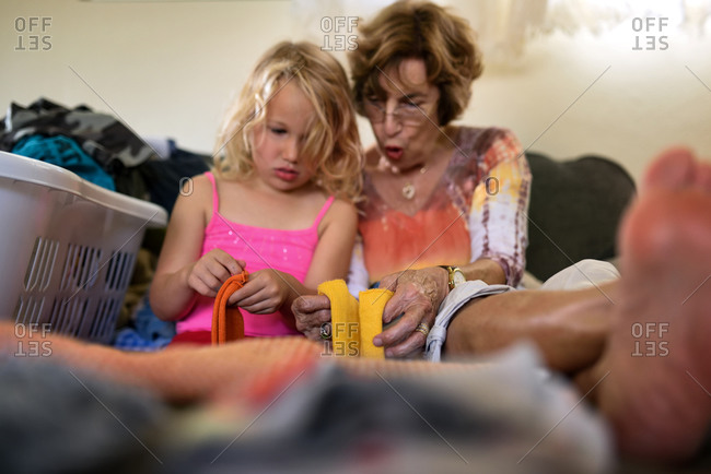 Grandmother and granddaughter fold socks on sofa