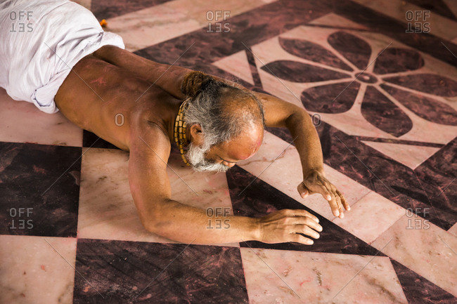 Nandgaon, India - March 10, 2013: Man prays while lying on the floor of Nandgaon temple