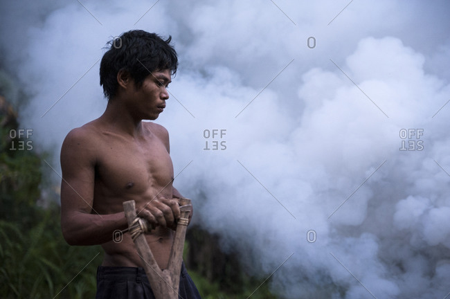 Singnapan, Rizal Province, Southern Palawan, Philippines - April  20, 2012: Tau't Bato trying to keep mosquitoes away with smoke