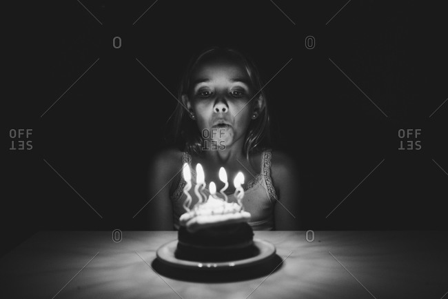 A girl blows out candles on a cake