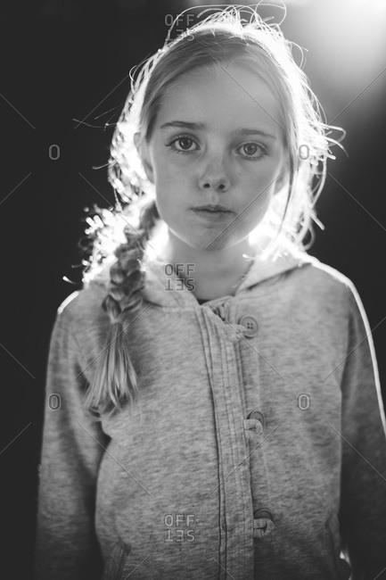 A girl stands in front of a spotlight