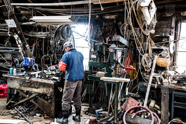 Man surrounded by wires and cables in a messy workshop