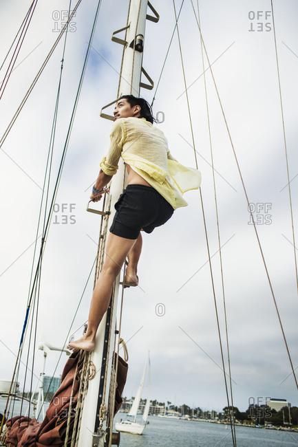 A man climbs a mast of a sailboat