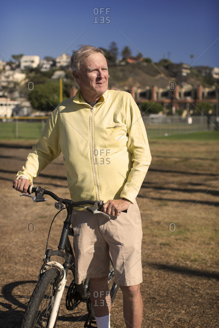 An older man walks with his bike