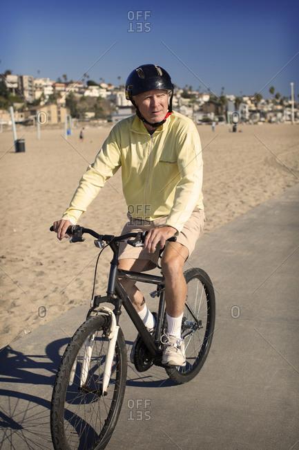 An older man rides his bike along the beach