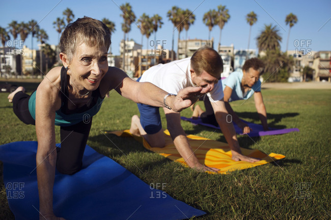 A group of older people practice yoga