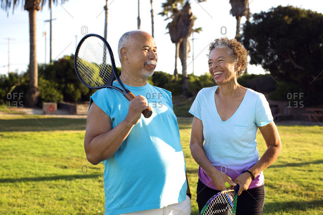 An older couple with tennis rackets