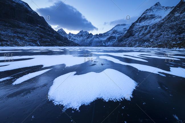 Patterns of snow cover black ice of Lake Ågvatnet in winter, Å i Lofoten, Moskenesøya, Lofoten Islands, Norway