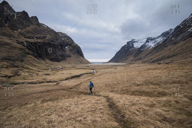 Female hiker hiking trail towards Horseid beach, Moskenesøya, Lofoten Islands, Norway