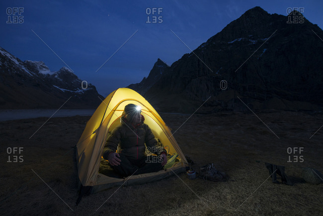 Female hiker sits in tent illuminated at night while wild camping at scenic Horseid beach, Moskenesøya, Lofoten Islands, Norway