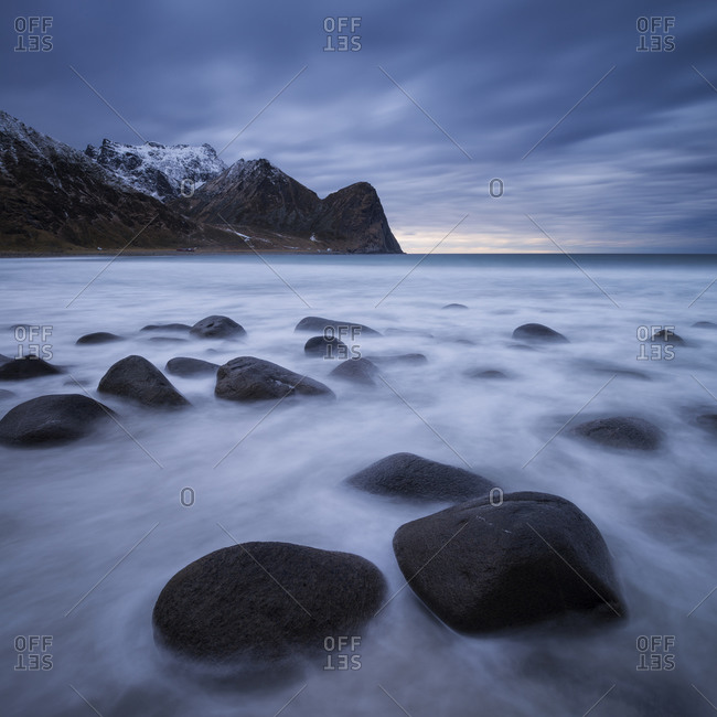 Waves flow among boulders at scenic Unstad beach, Vestvågøy, Lofoten Islands, Norway