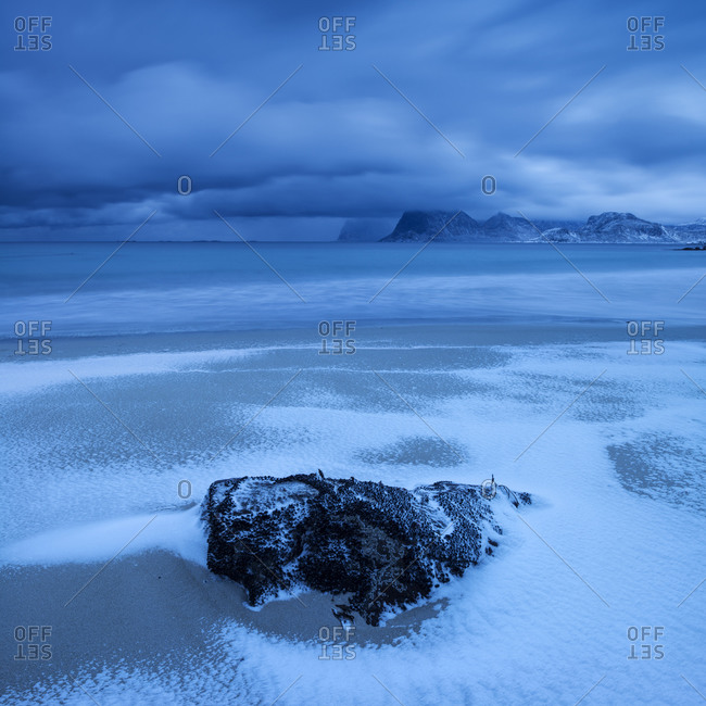 Waves wash over snow covered sand in winter at Storsandnes beach, Flakstadøya, Lofoten Islands, Norway