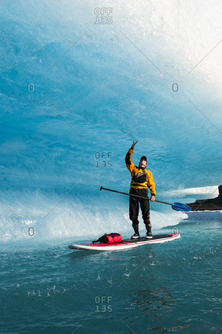 A man on a stand up paddle board touches a wave of ice as it drips and melts on Bear Lake in Kenai Fjords National Park, Alaska