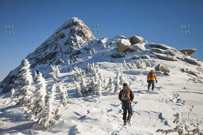 Two climbers wearing backpacks walk a snow-covered ridge in the Coquihalla Recreation Area of British Columbia, Canada
