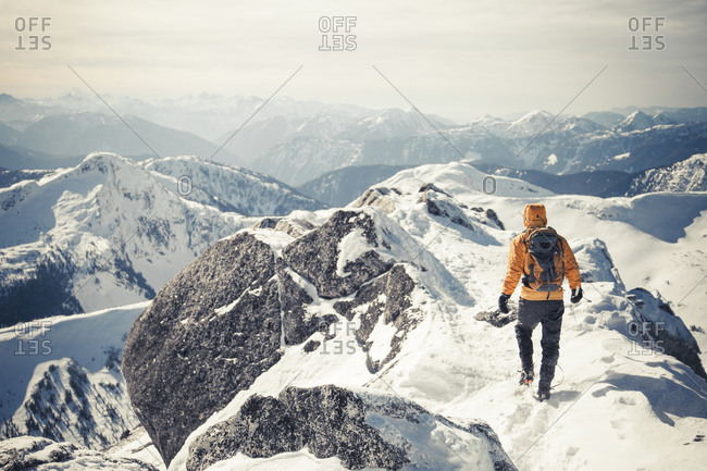 A climber walks a mountain ridge during winter in the Coquihalla Recreation Area of British Columbia, Canada