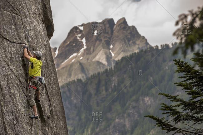 Italian climber trad climbing a crack route in Esigo, Ossola, Italy