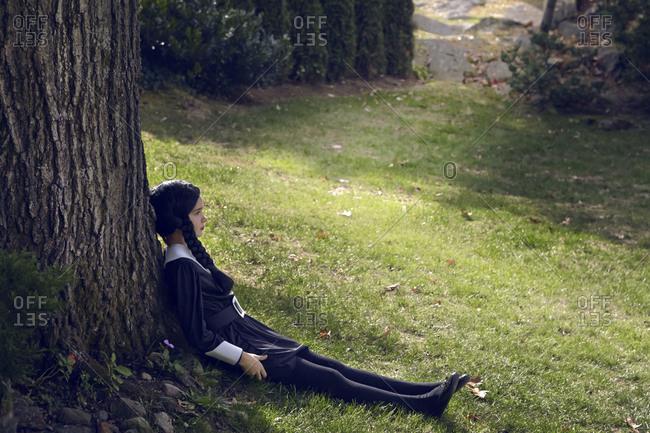 Costumed girl leans against tree