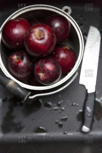 Overhead view of pail of fresh red apples and a knife
