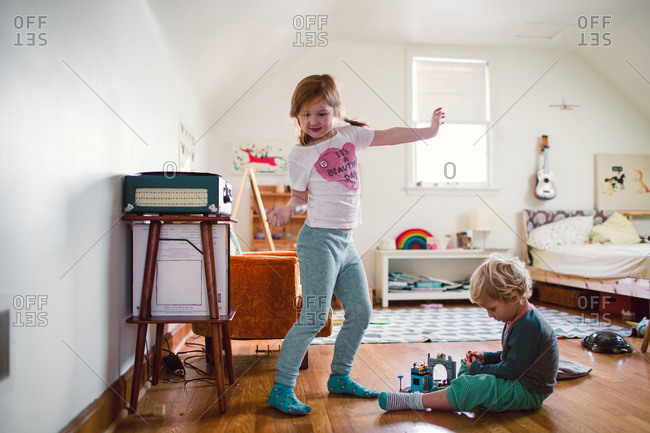 A brother and sister play in a bedroom