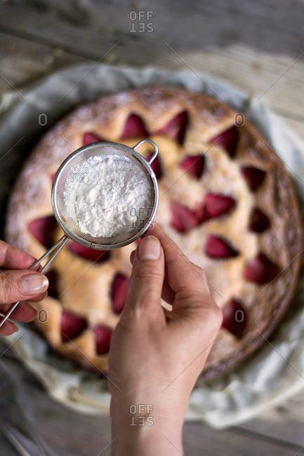 Sifting sugar onto a strawberry cake