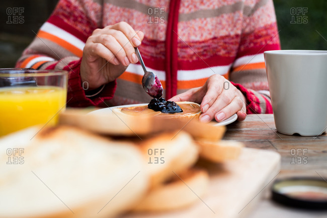 Woman spooning jam on peanut butter and bread