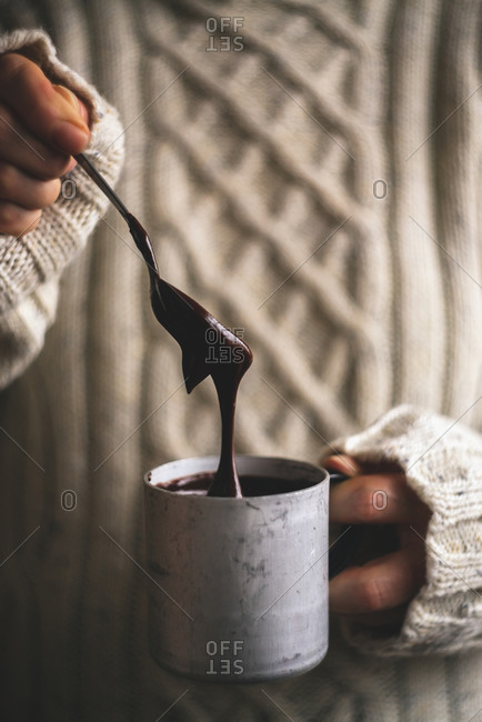 Woman holding mug of melted chocolate
