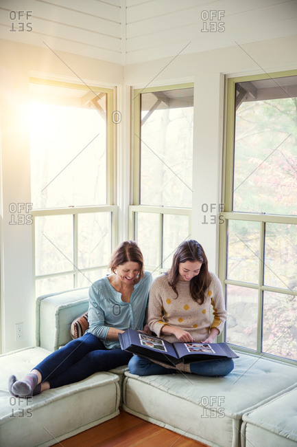 Mother and adult daughter smile while looking at photo album