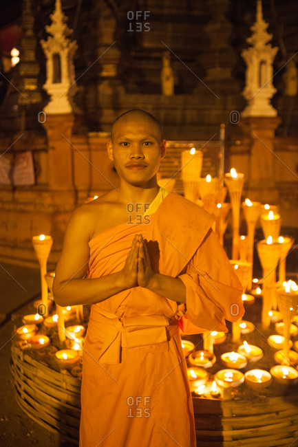 Chiang Mai, Thailand - June 11, 2014: Glowing butter lamps behind a Buddhist monk