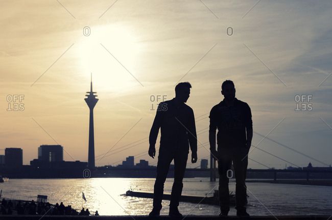 Two man looking to Rhine tower and Rhine river at sunset, Dusseldorf