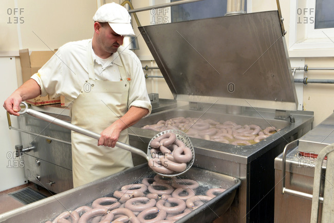 Man taking cooked sausages from cauldron in a butchery