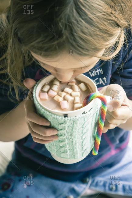 Young girl drinking hot chocolate with marshmallows