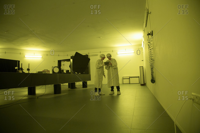 Female technicians working in optical cleanroom unit