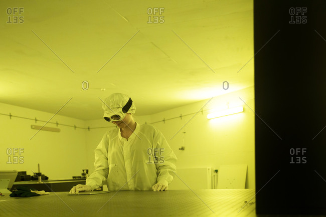 Female technician working in optical clean room unit