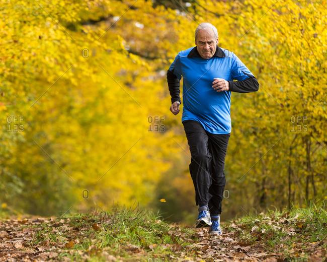 Senior man running in autumnal forest