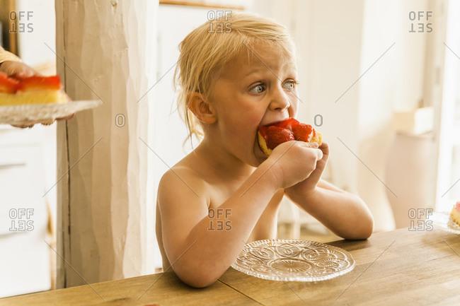 Blond girl eating strawberry cake