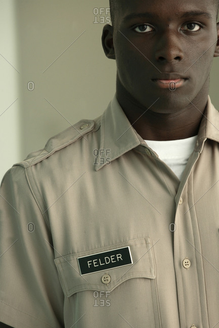 A young handsome African American male stands firm wearing his uniform.