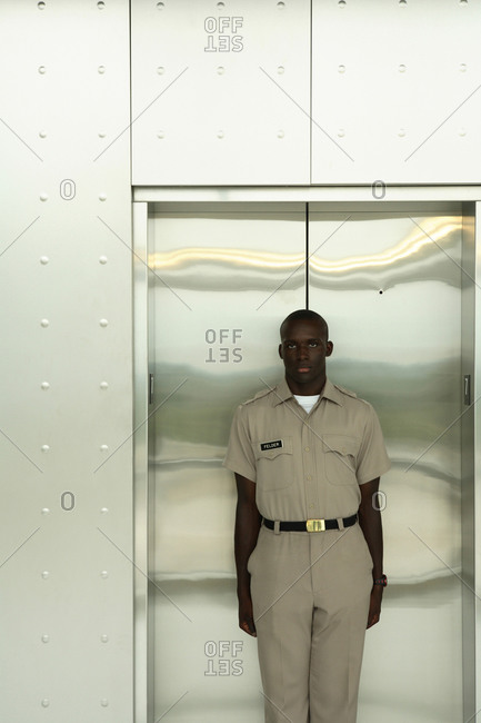 A young handsome African American male stands firm in front of an elevator wearing his uniform.