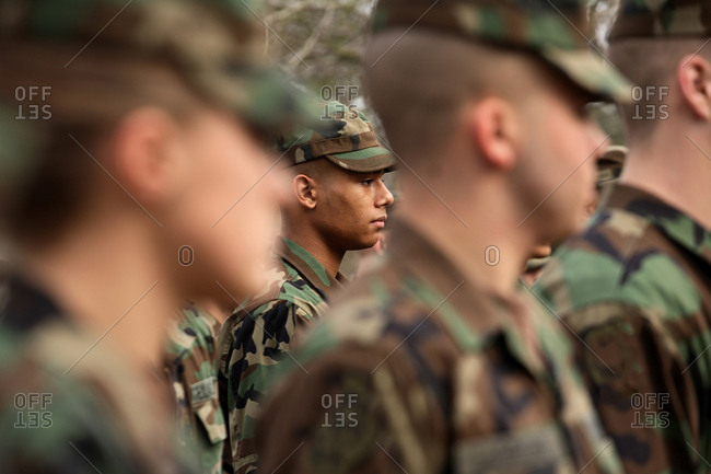 A young black male cadet stands firm during a class call as he holds on to his rifle and wears a uniform.